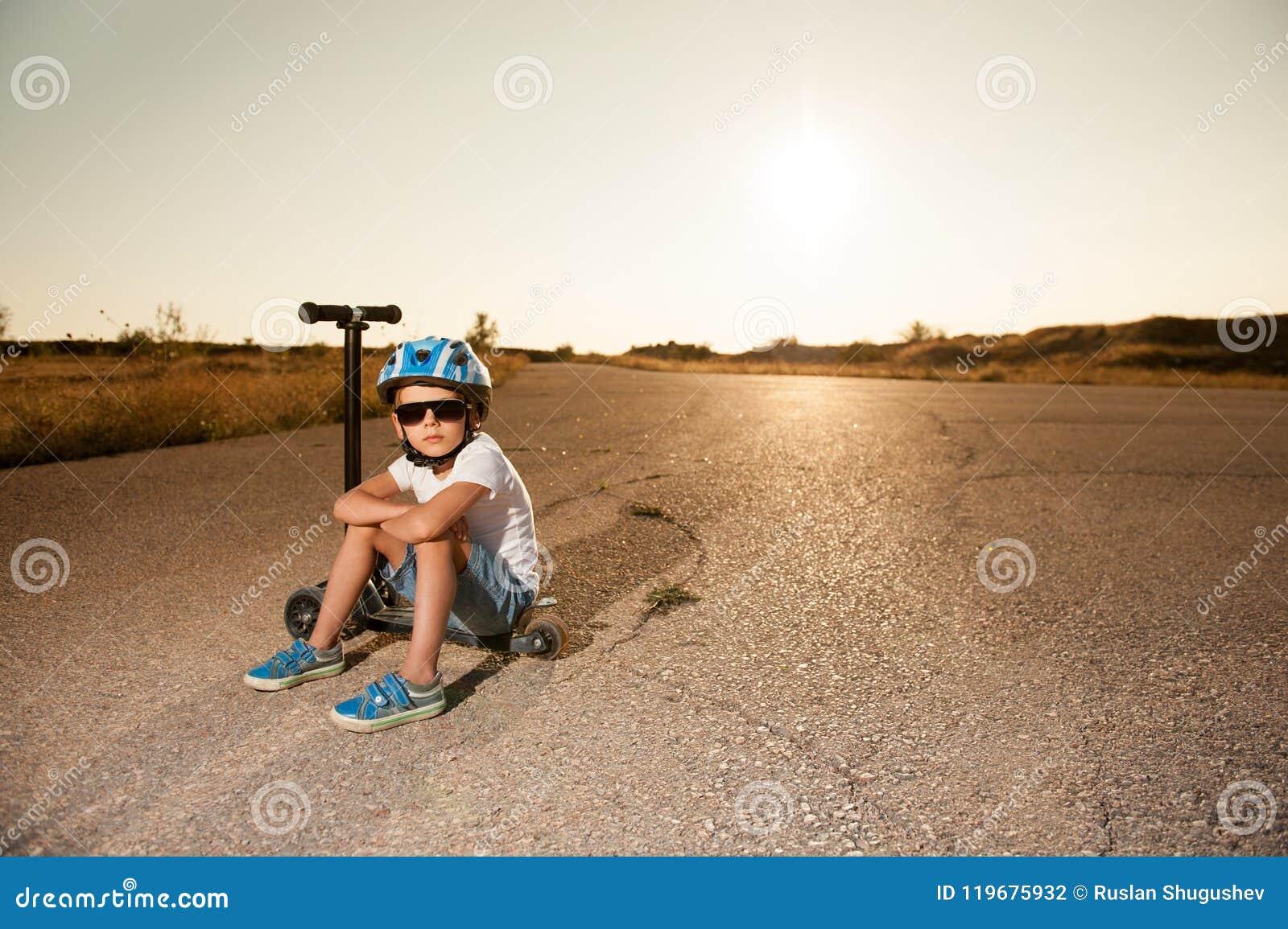 Hübscher kleiner Junge in der Sonnenbrille und Sturzhelm, der auf Roller auf verlassener Straße sitzt