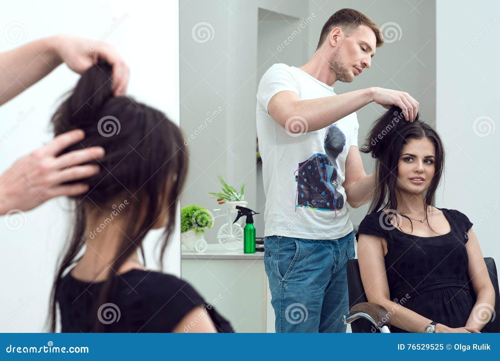 Hübscher männlicher Friseur stellt das Haar her, das für seinen Kunden am Schönheitssalon anredet