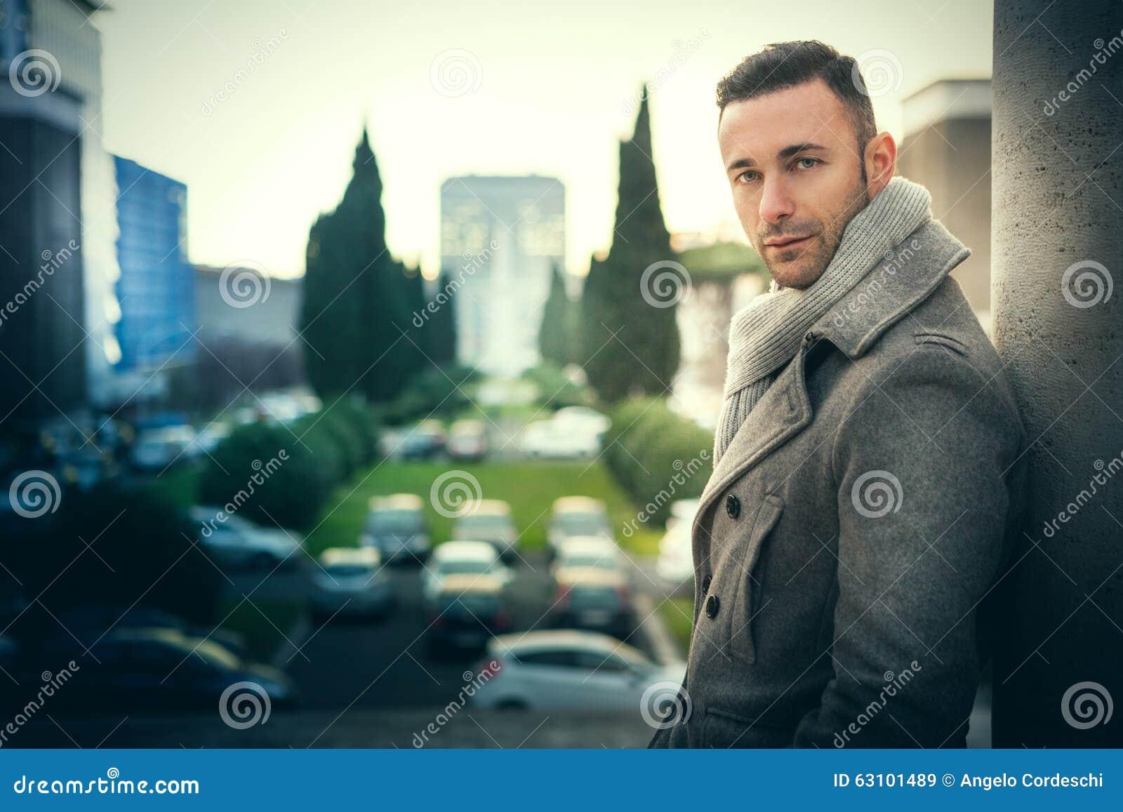 Hübscher moderner Mann in der Stadt Die Mode der Wintermänner