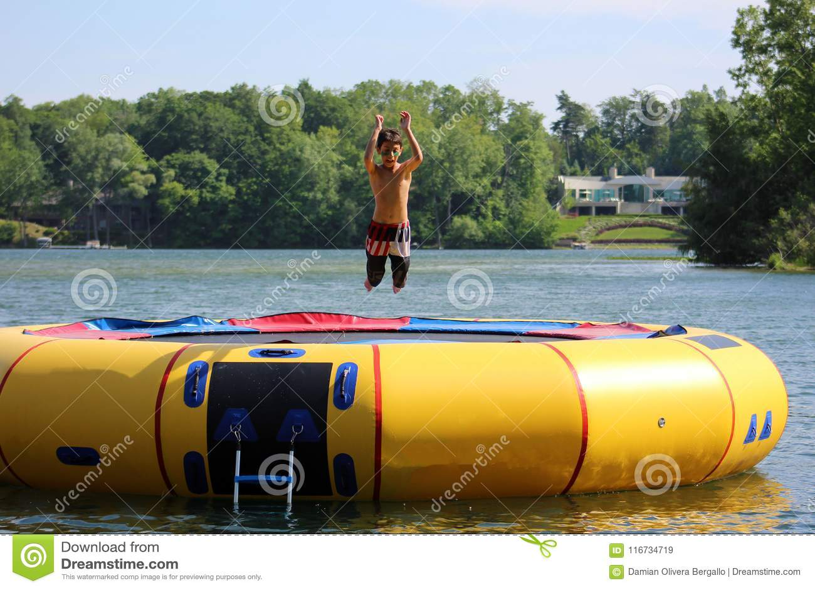 Hübscher netter Junge, der an einer Wassertrampoline schwimmt in einen See in Michigan während des Sommers springt
