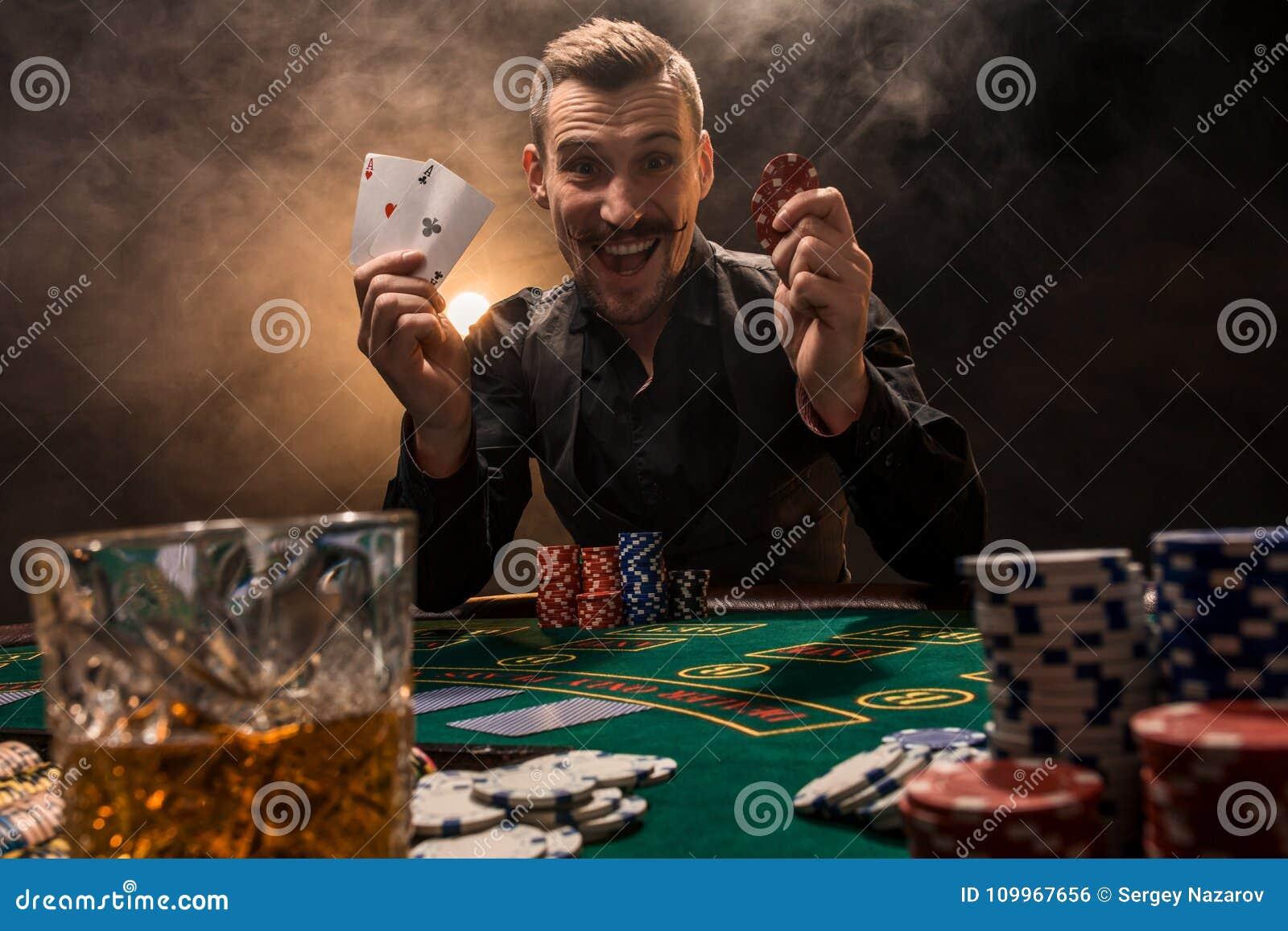 Hübscher Pokerspieler mit zwei Assen in seinen Händen und in Chips, die voll am Pokertisch in einer Dunkelkammer des Zigarettenra