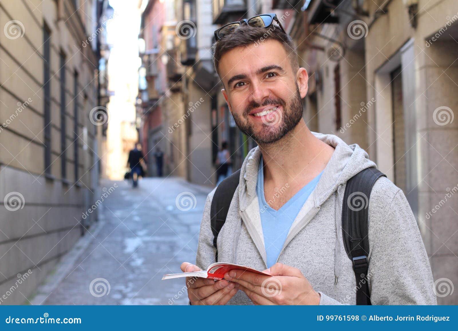 Hübscher Student, der auf dem Campus lächelt