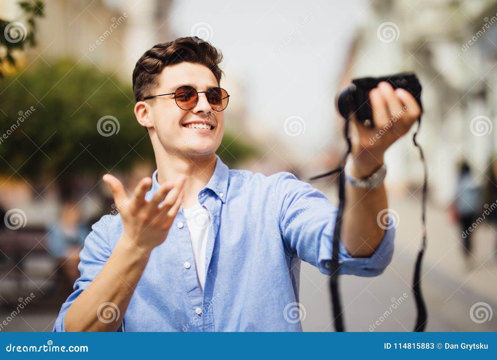 Hübscher Tourist, der ein selfie an der Berufung nimmt Junger Mann, der an der Kamera in einer städtischen Szene lächelt Kaukasis