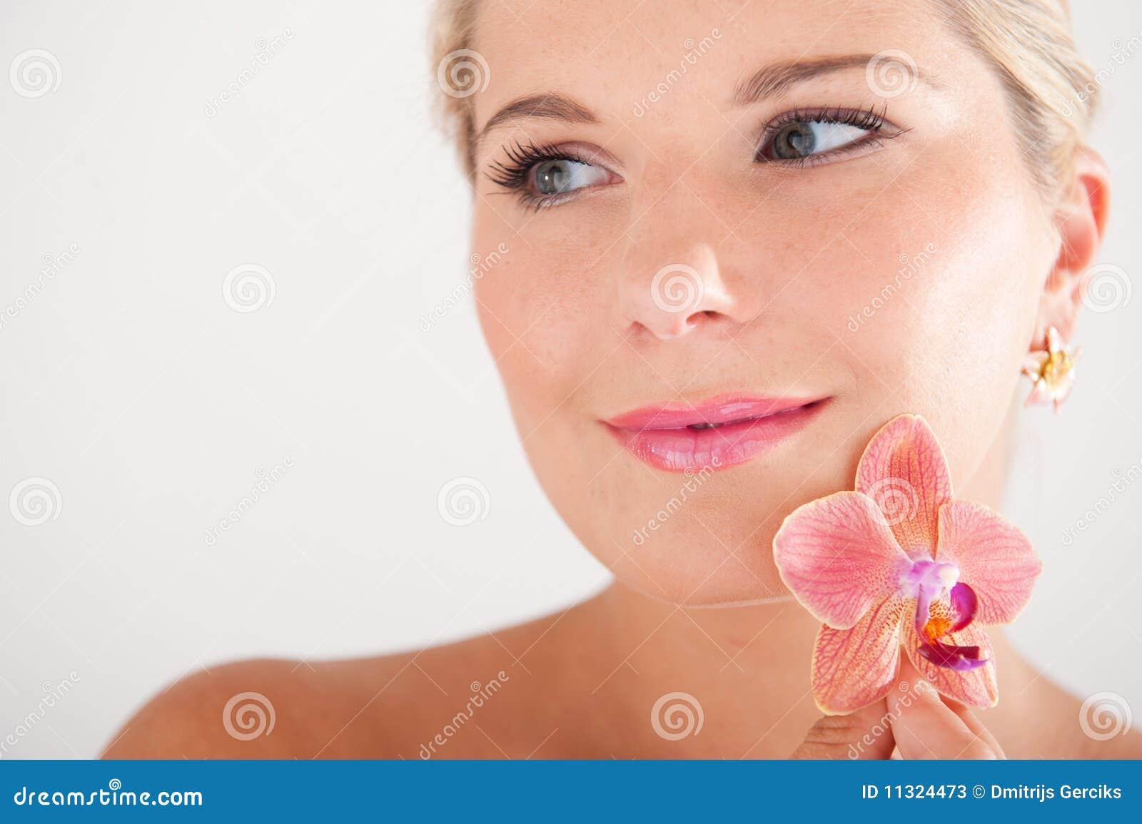 Hübsches Frau whith reine gesunde Haut und Orchidee