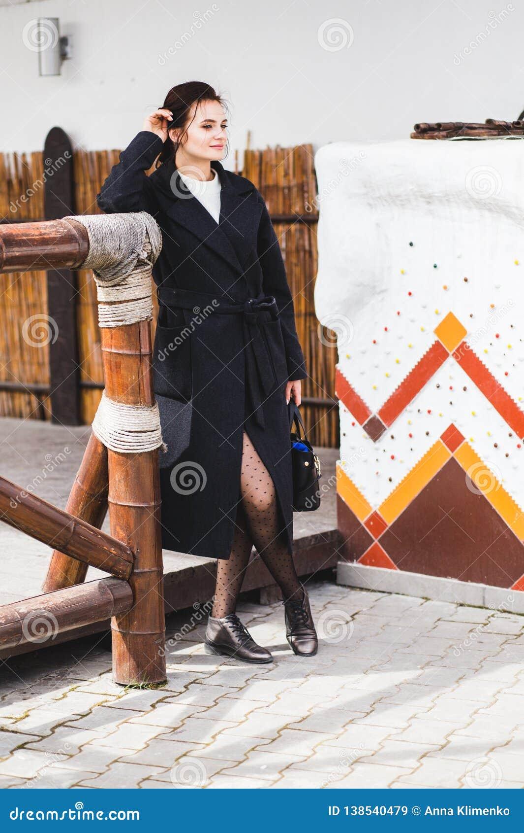 Hübsches Frauenmodell der Mode, das einen dunklen Mantel und eine weiße Strickjacke aufwerfen über ethnischem Hintergrund trägt