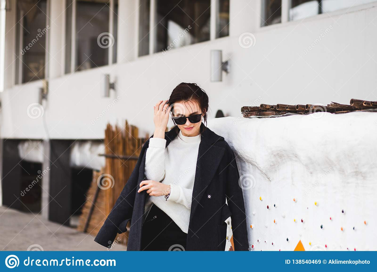 Hübsches Frauenmodell der Mode, das einen dunklen Mantel und eine weiße Strickjacke, in der Sonnenbrille, werfend über weißem Hin