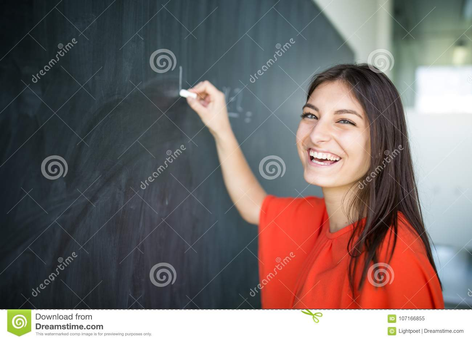 Hübsches, junges Studentschreiben auf der Tafel