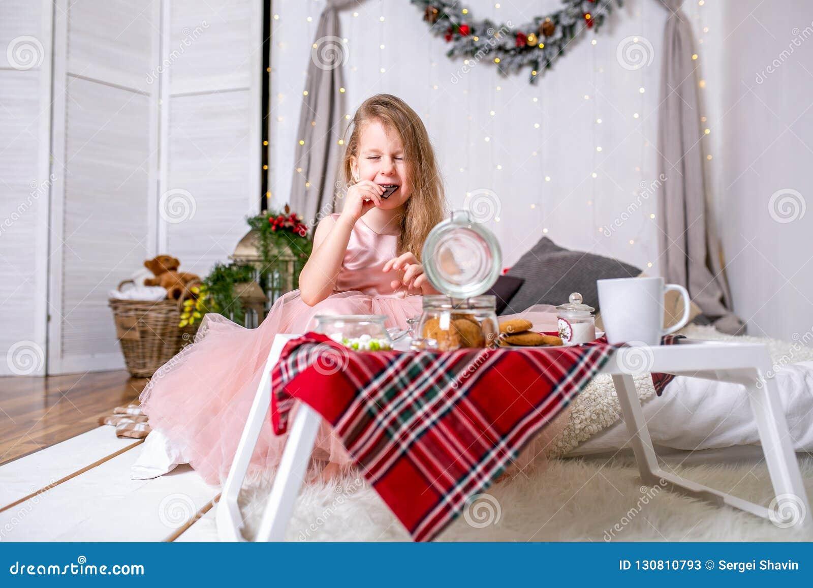 Hübsches kleines Mädchen 4 Jahre alt in einem rosa Kleid Kind im Weihnachtsraum mit einem Bett, Süßigkeit, Schokolade, Plätzchen