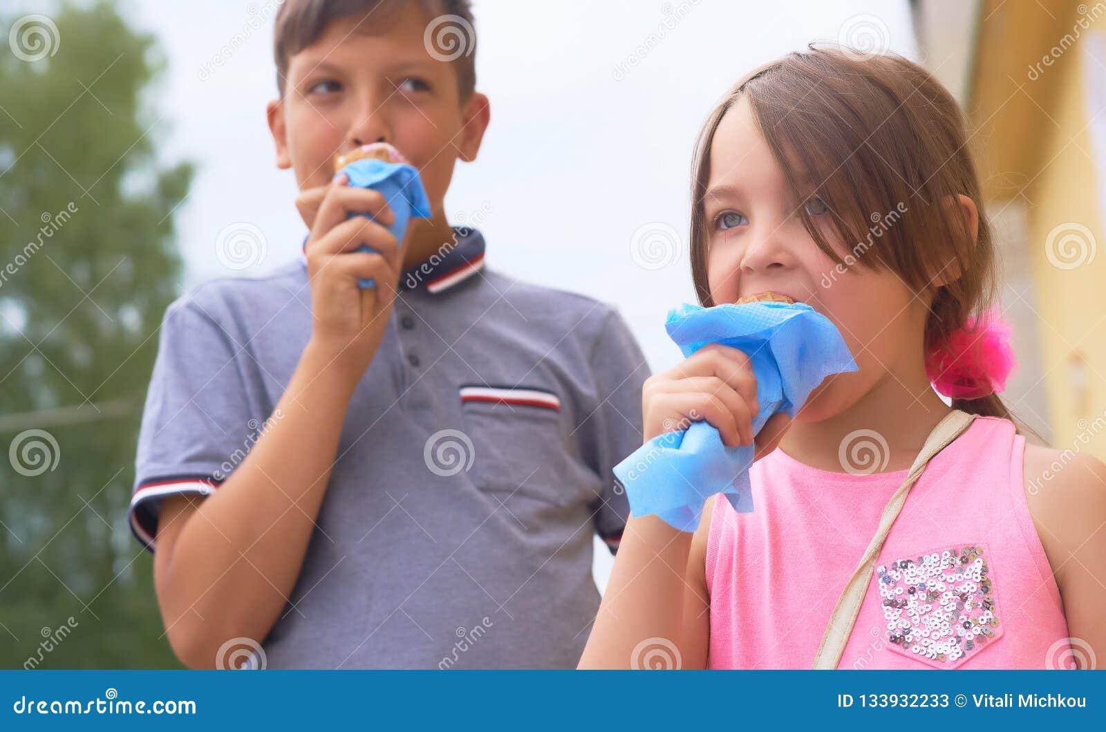 Hübsches kleines Mädchen und lächelnder Teenager, die große Eiscreme im glücklichen Lachen des Waffelkegels auf Naturhintergrund