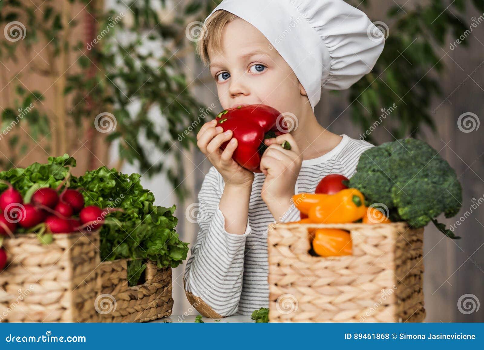 hübsches kleinkind in der chefuniform mit gemüse in der küche zu ... - Kleinkind Küche