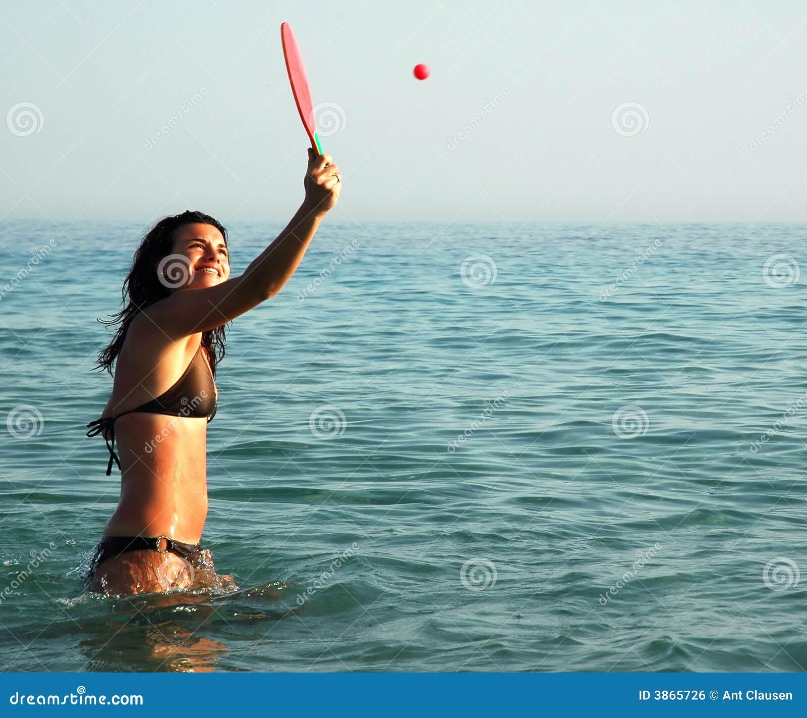 Hübsches Mädchen, das Kugel im Ozean spielt