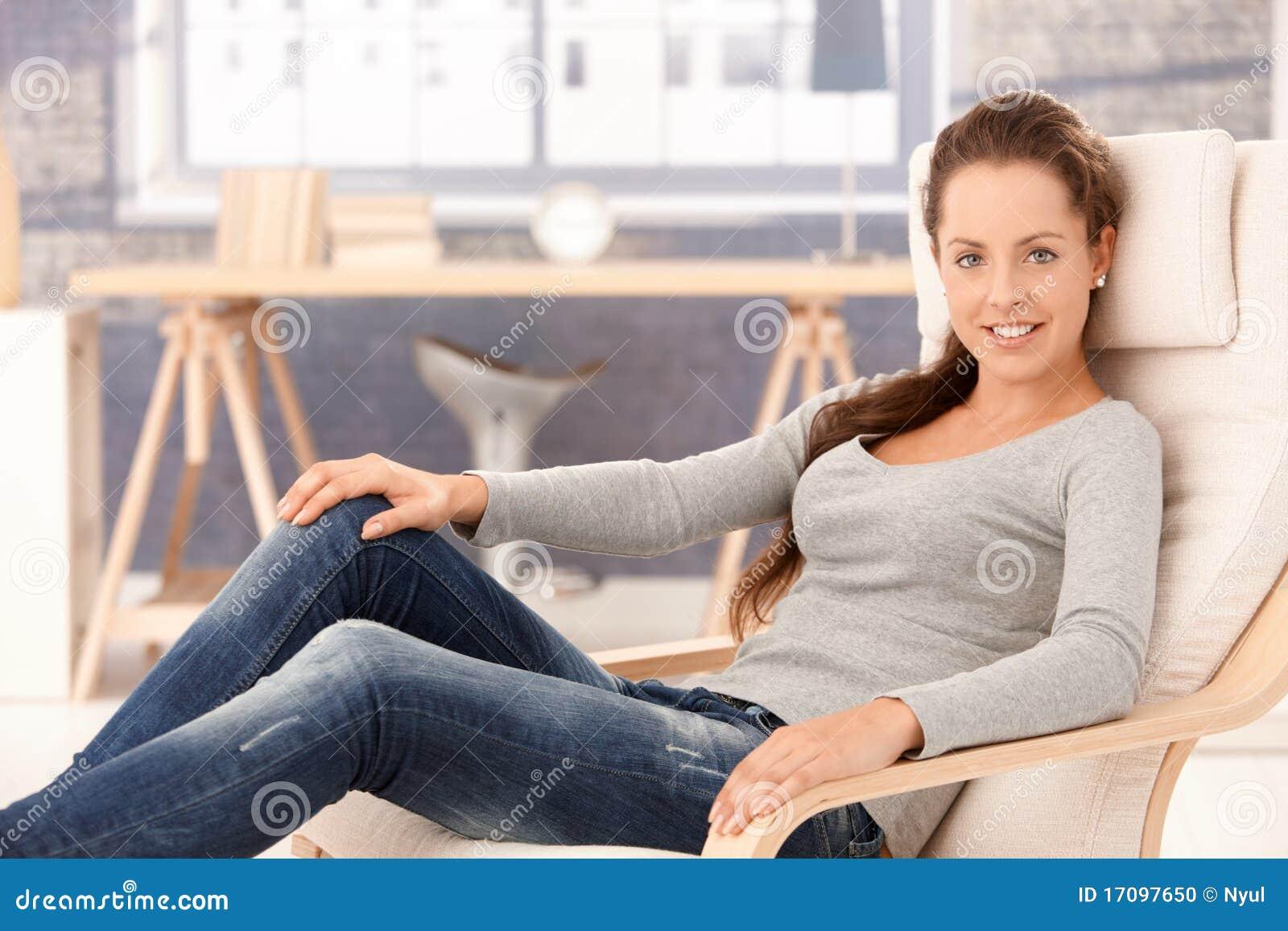 Hübsches Mädchen, das sich zu Hause beim Lehnsessellächeln entspannt