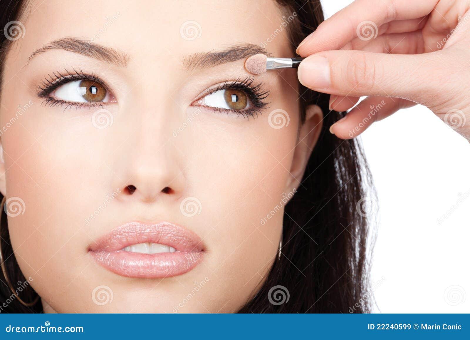 Hübsches Mädchen empfängt Augenschminke vom Verfassungskünstler