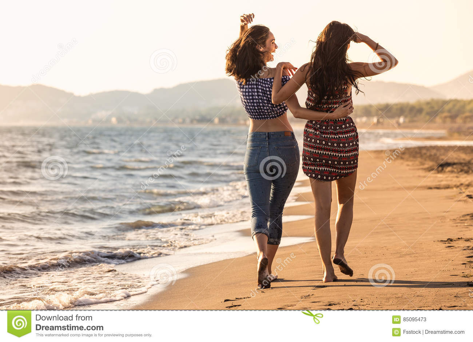 Hübsches Mädchen hat einen Spaß mit ihrer Freundin auf dem Strand