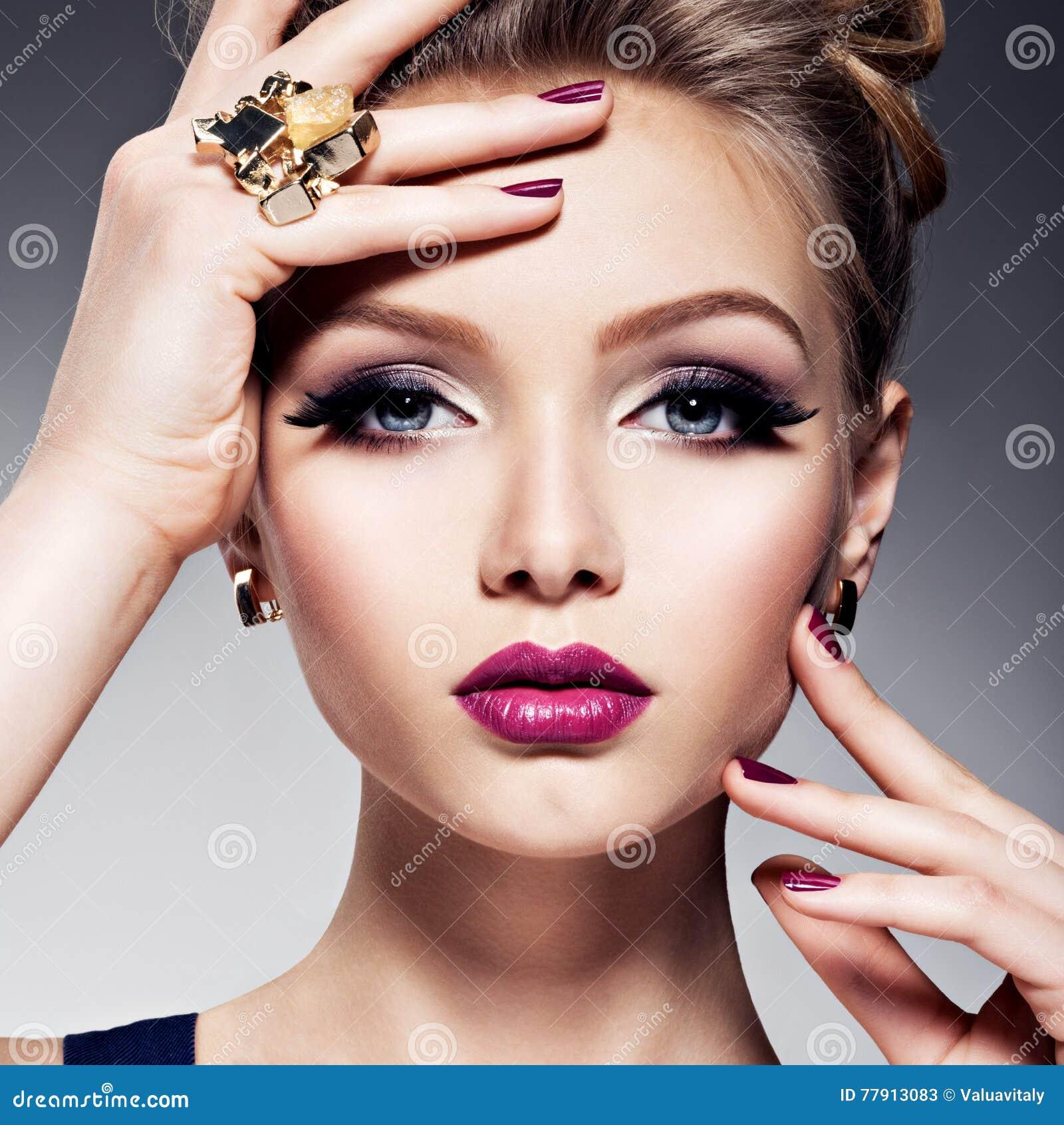 Hübsches Mädchen mit hellem Make-up des schönen Gesichtes und Goldschmuck