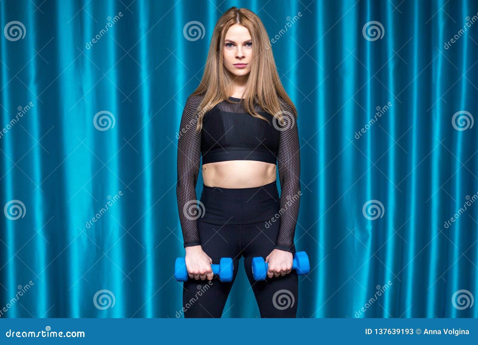 Hübsches sportliches Mädchen, das Übungen mit Dummköpfen tut