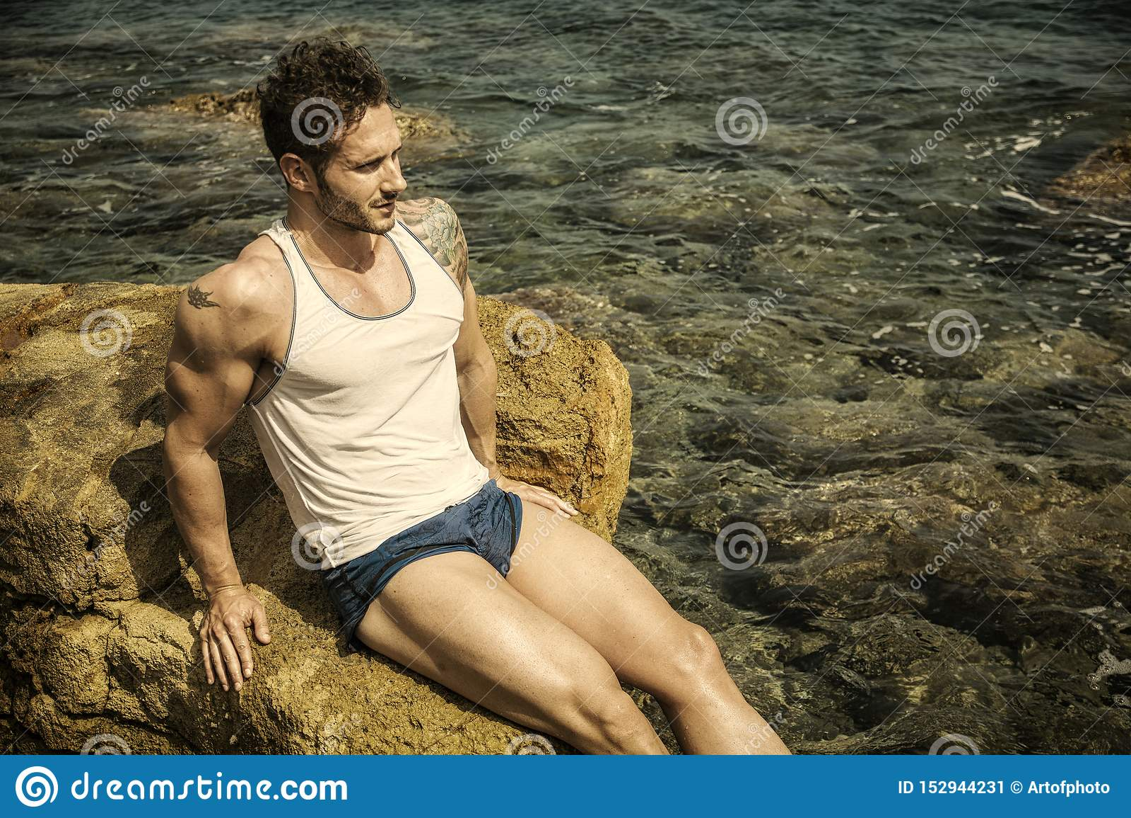 H?bscher muskul?ser Mann auf dem Strand, der auf Felsen sitzt