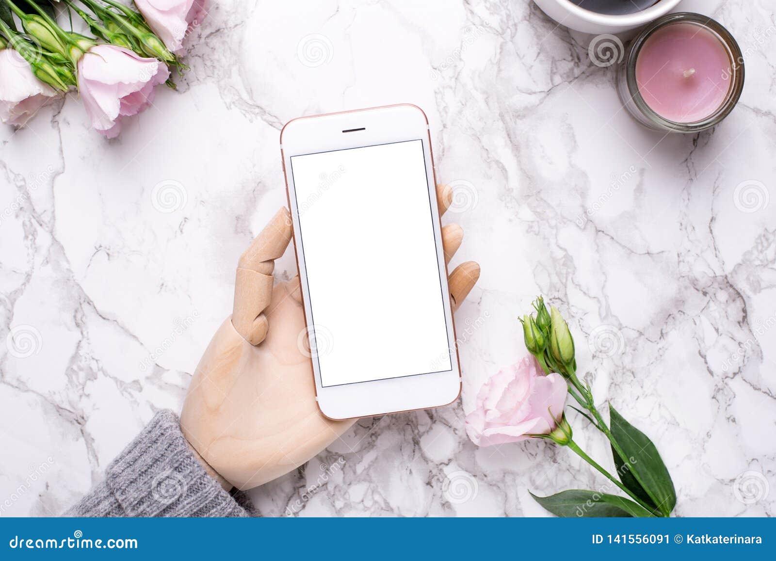 H?lzerne Hand mit Handy auf Marmorb?rohintergrund mit rosa Blumen