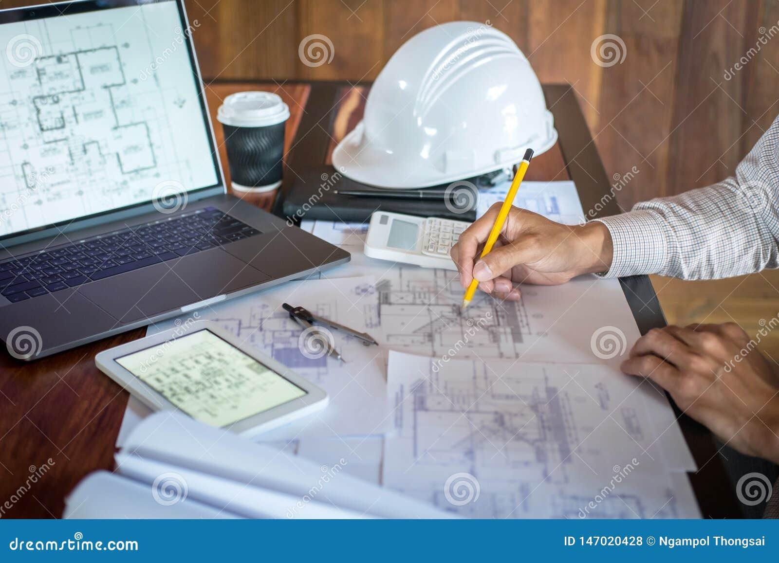 H?nder f?r konstruktionsteknik som eller arkitektarbetar p? ritningkontroll i arbetsplats, medan kontrollera informationsteckning