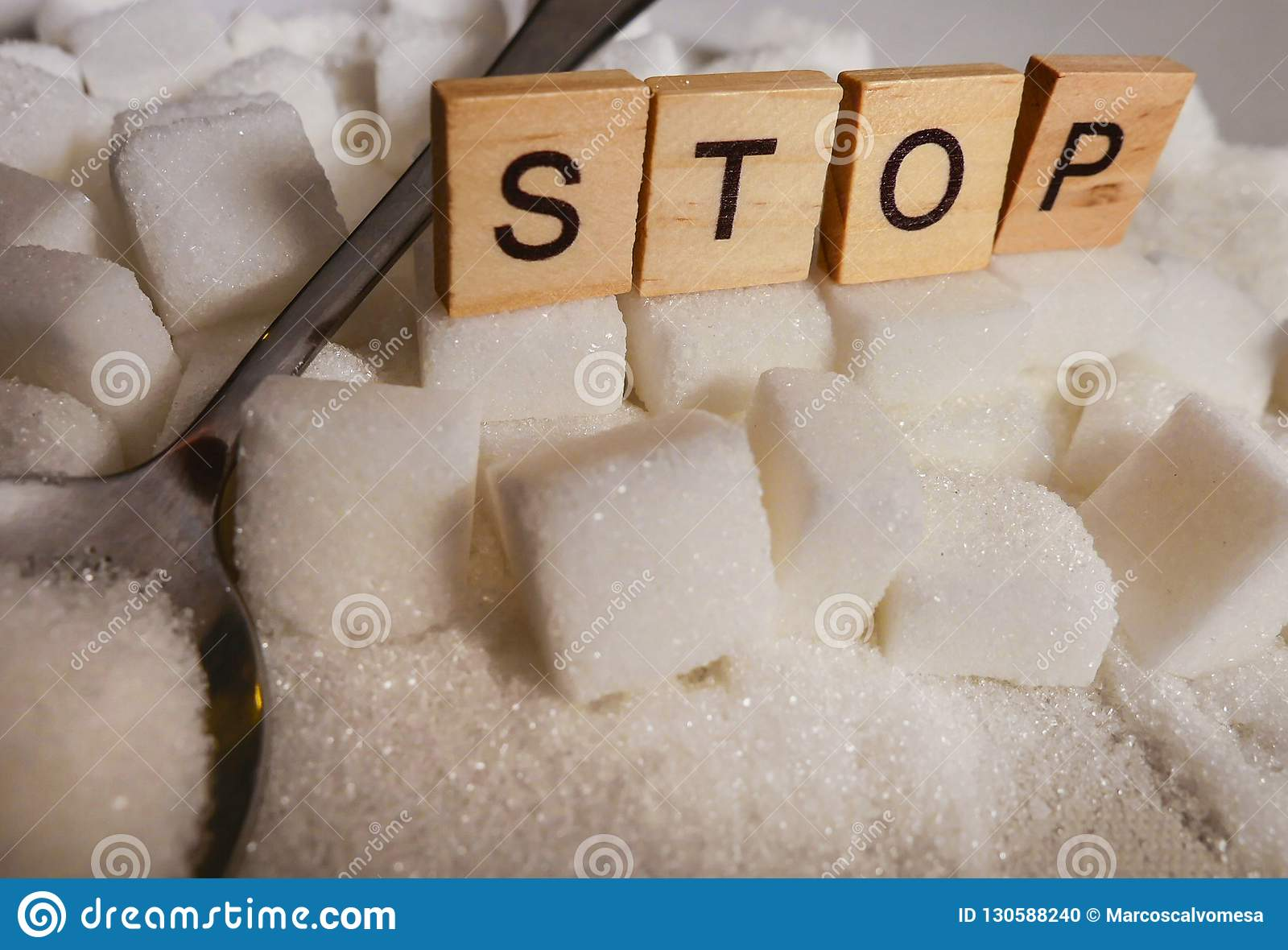 H pile of white sugar cubes and stop word in block letters as advise on addiction calories excess and sweet unhealthy food abuse c