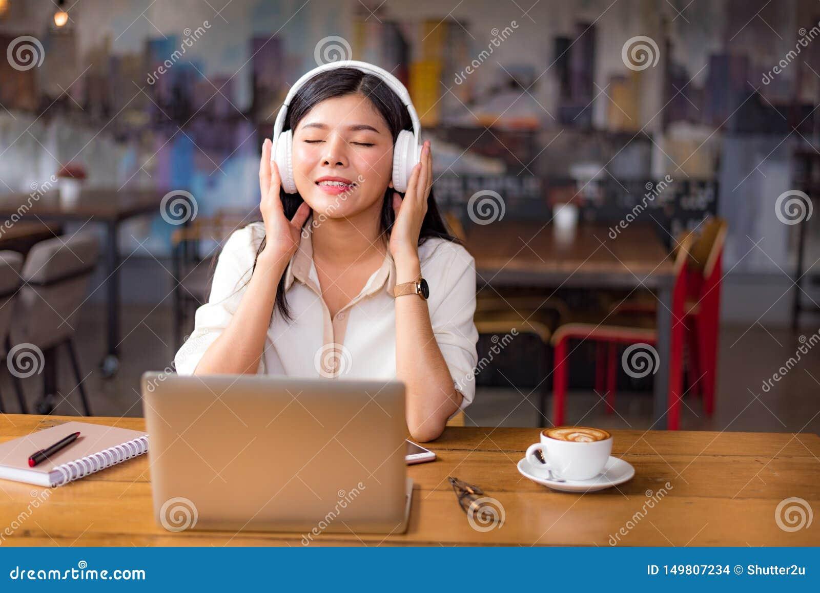 H?rlig asiatisk kvinna som kopplar av och lyssnar till musik i kaf? med b?rbar datordatoren och kaffekoppen Folk och livsstilbegr