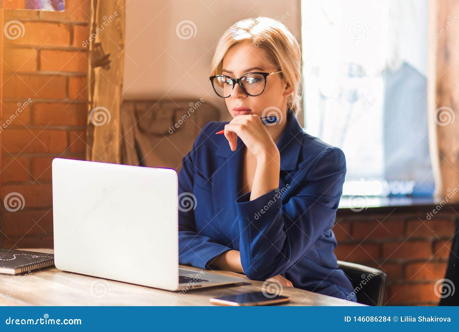 H?rlig klyftig aff?rskvinna som sitter p? tabellen p? arbetsstationen med b?rbara datorn