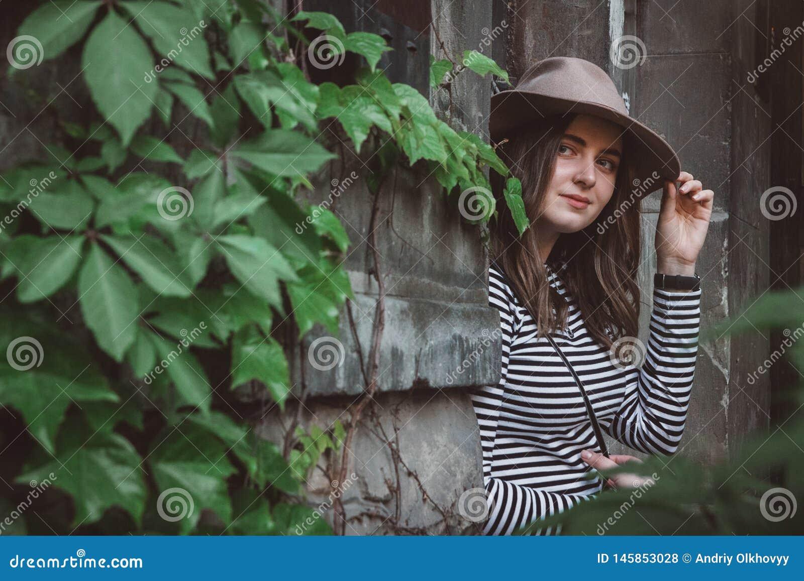 H?rlig kvinna i en randig skjorta som rymmer hennes hatt och ser en kamera