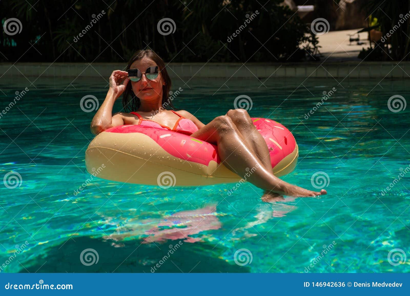 H?rlig kvinna och uppbl?sbar badcirkel i form av en munk i p?len