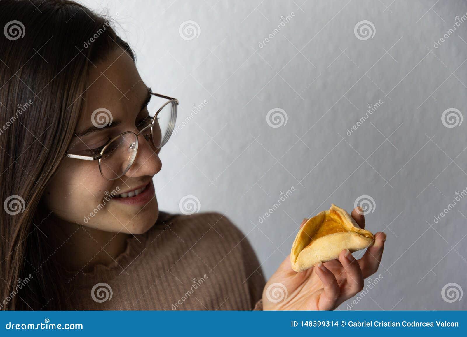 H?rlig och lycklig kvinnast?ende som ?ter kakan f?r hamantashPurim aprikos