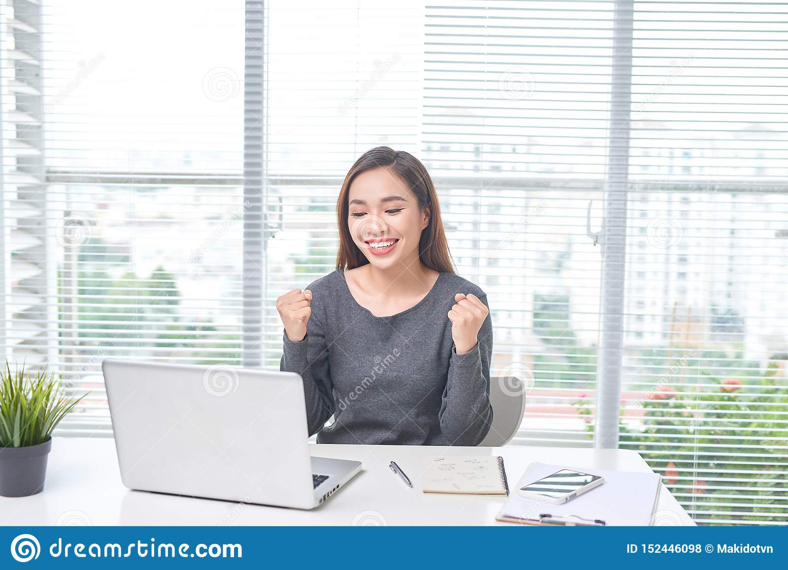 H?rlig ung asiatisk kvinna med en sp?nnande b?rbar dator