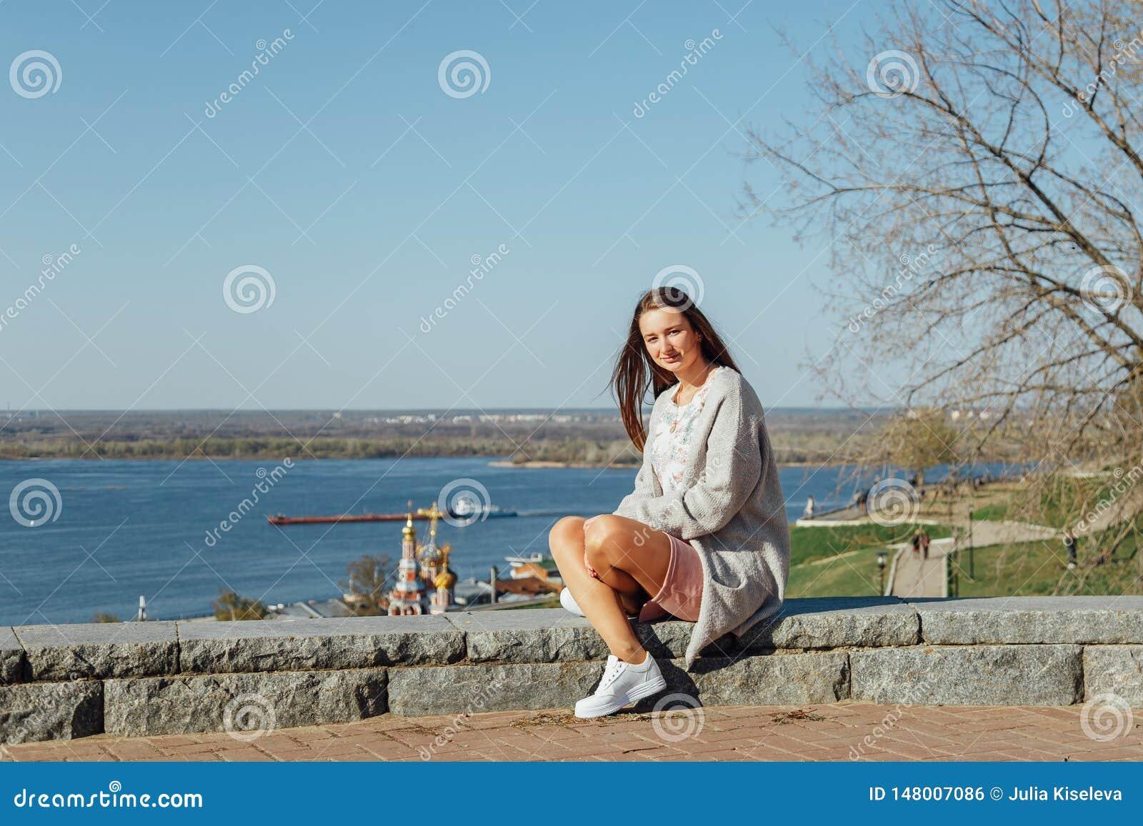 H?rlig ung flicka som sitter p? den Volga River invallningen