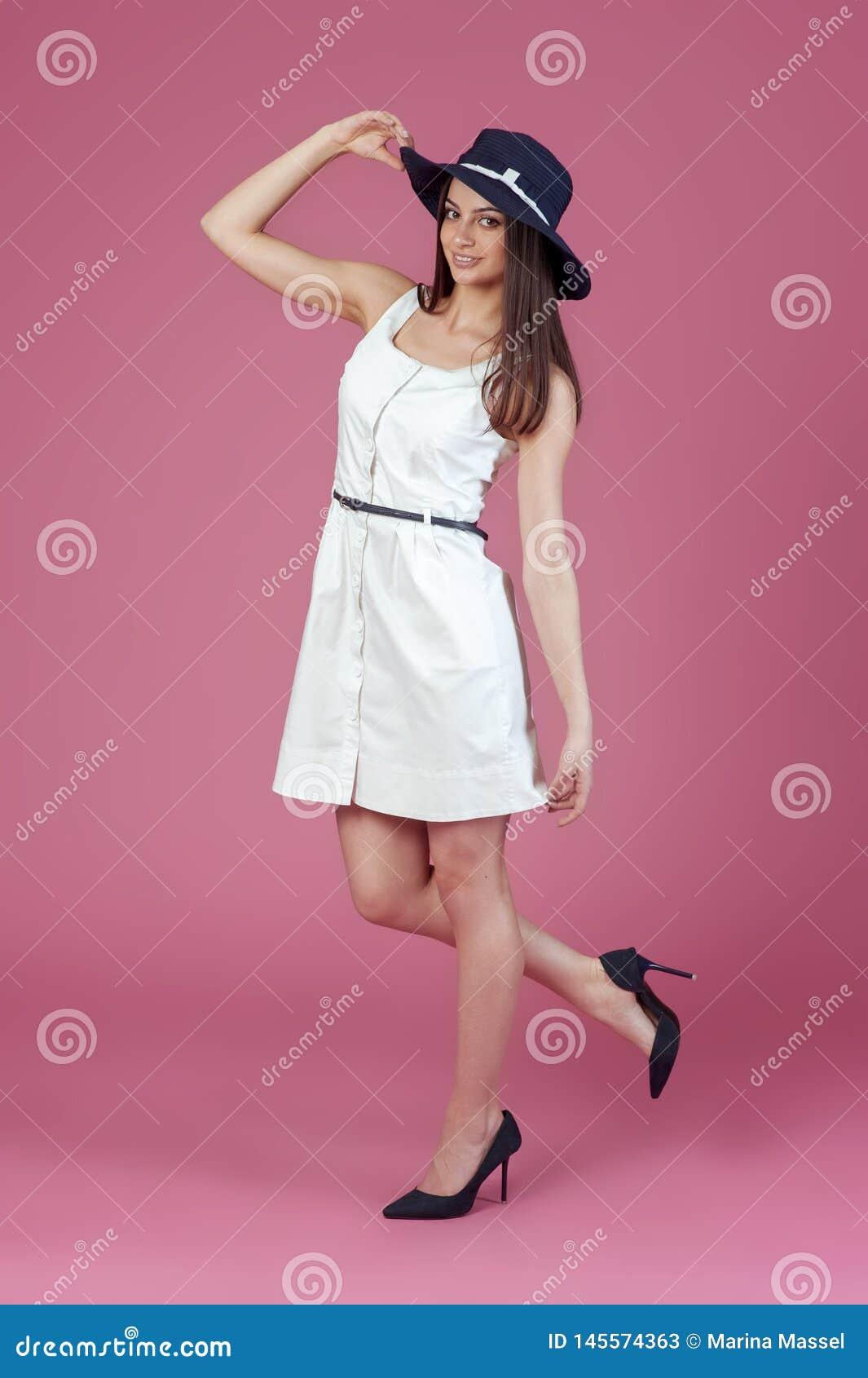 H?rlig ung kvinna i elegant vit kl?nning och sommarhatt Flicka som poserar p? en rosa bakgrund bedsheetmode l?gger f?rf?riskt vit