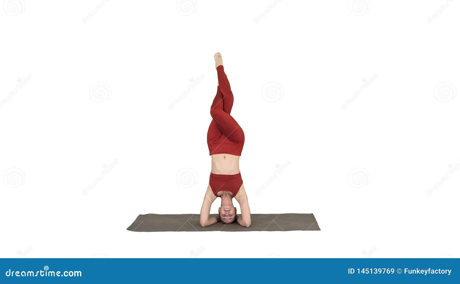 H?rlig ung kvinna som g?r yoga?vningsvariation av den st?ttade huvudst?enden, garudasalambasirsasana med korsade ben