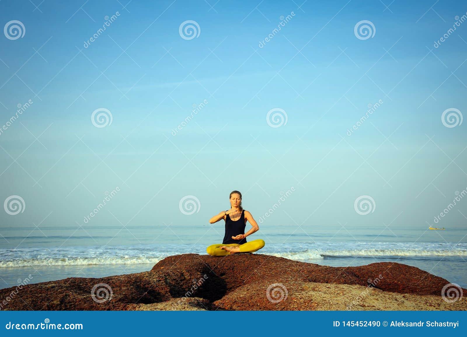 H?rlig ?vande yoga f?r ung kvinna och str?cknings?vningar p? sommarhavstranden