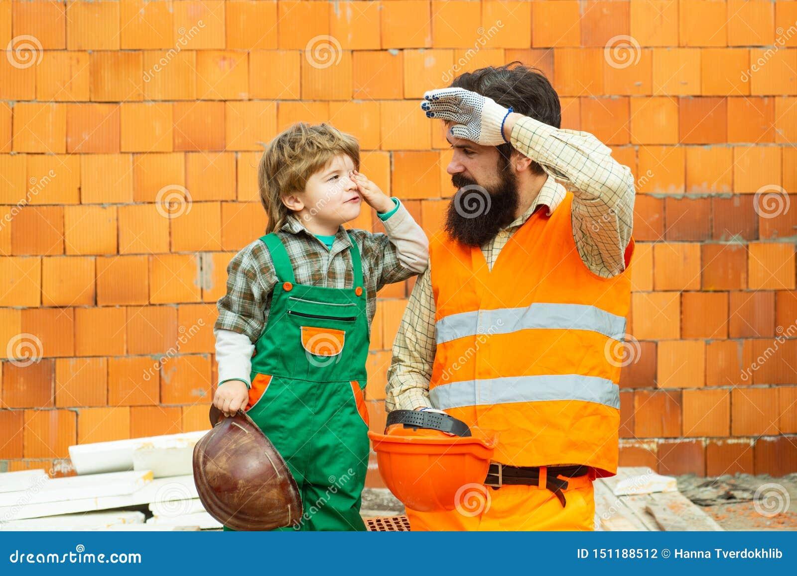 H?rt arbete Arbetsdags Ett lag av byggmästare är trött på arbete En man och en pojke i en dräkt av byggmästare