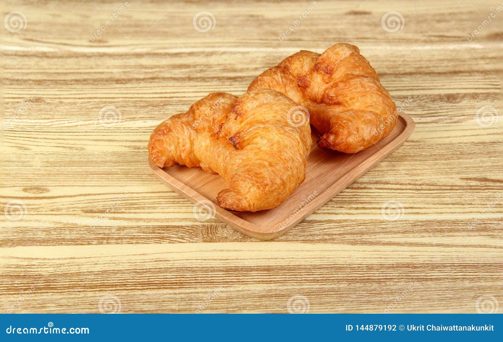Ha cotto di recente i croissant freschi e saporiti del croissant, isolati sul fondo di legno della tavola