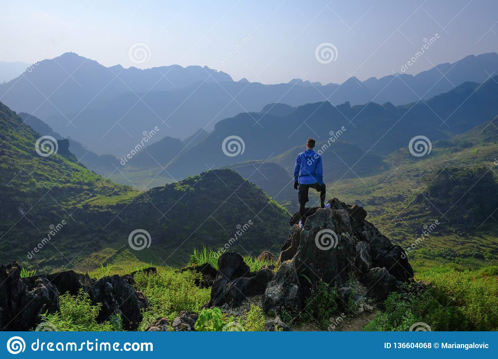 Ha Giang / Vietnam - 01/11/2017: Backpacker standing on outcrop overlooking karst mountain scenery in the North Vietnamese region