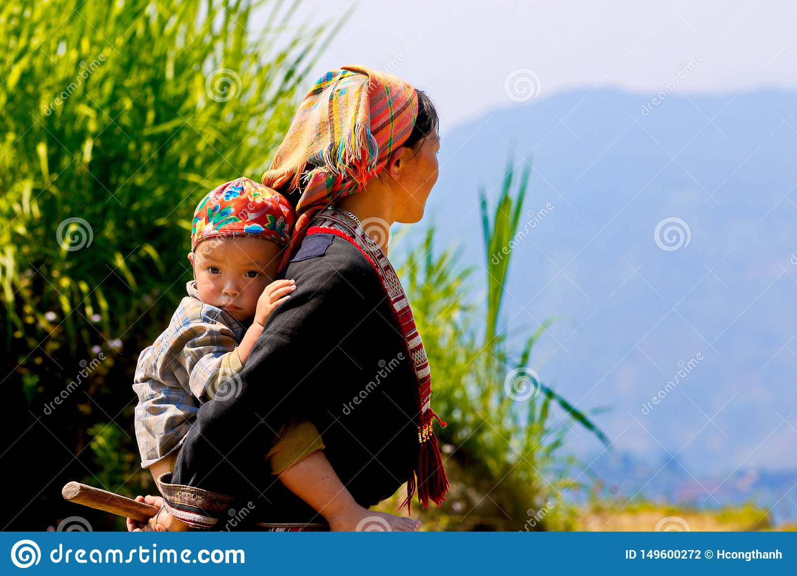 Ethnic mom and her child on the mountain near ripen rice terraces.