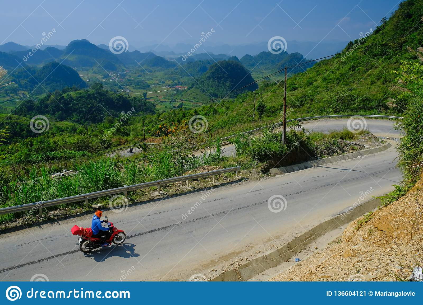 Ha Giang / Vietnam - 01/11/2017: Motorbiking backpackers on winding roads through valleys and karst mountain scenery in the North