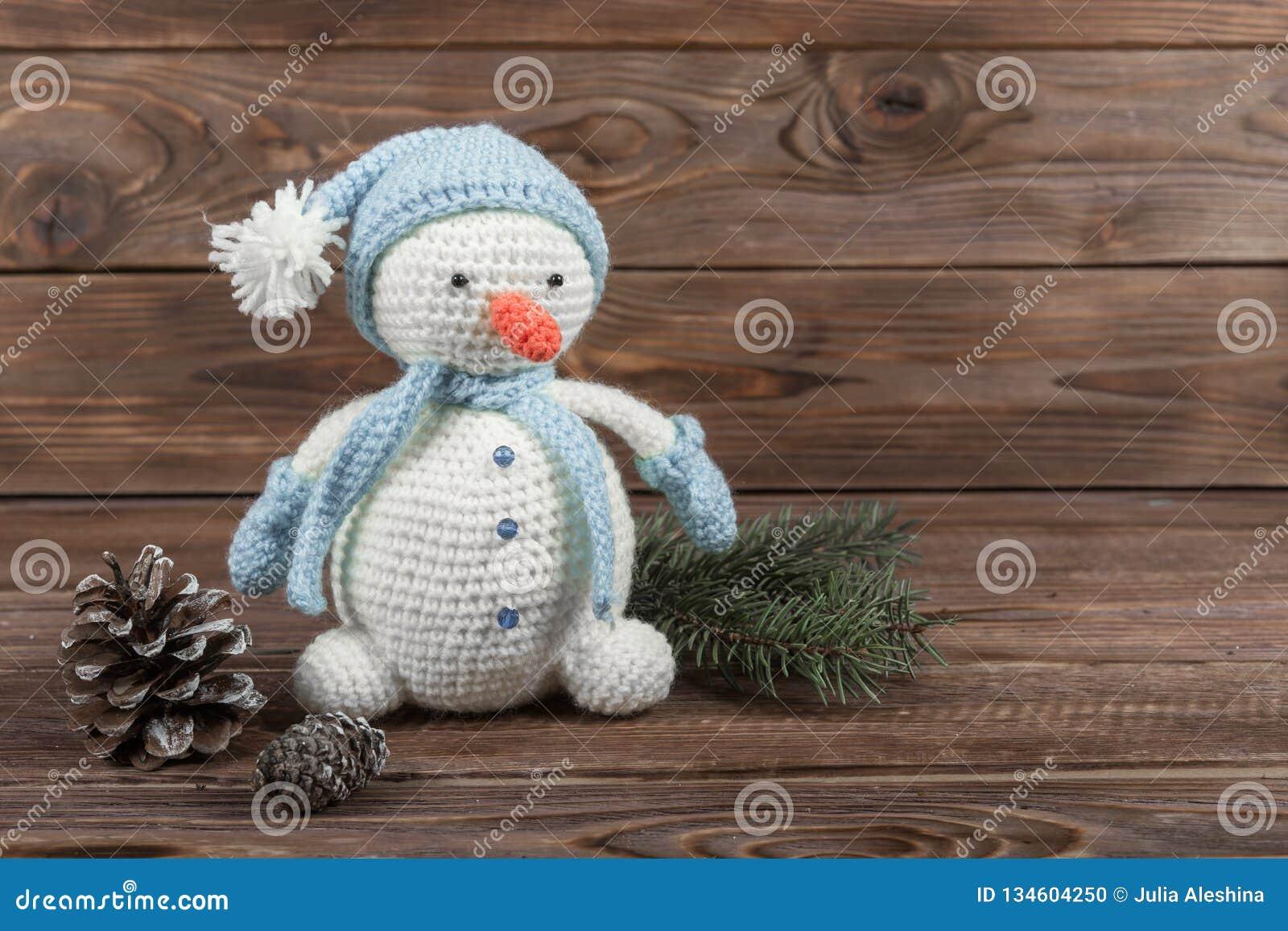 Haak kraftpapier-stuk speelgoed Witte sneeuwman in een blauwe hoed en sjaal op een donkere houten achtergrond Nieuwjaar` s giften