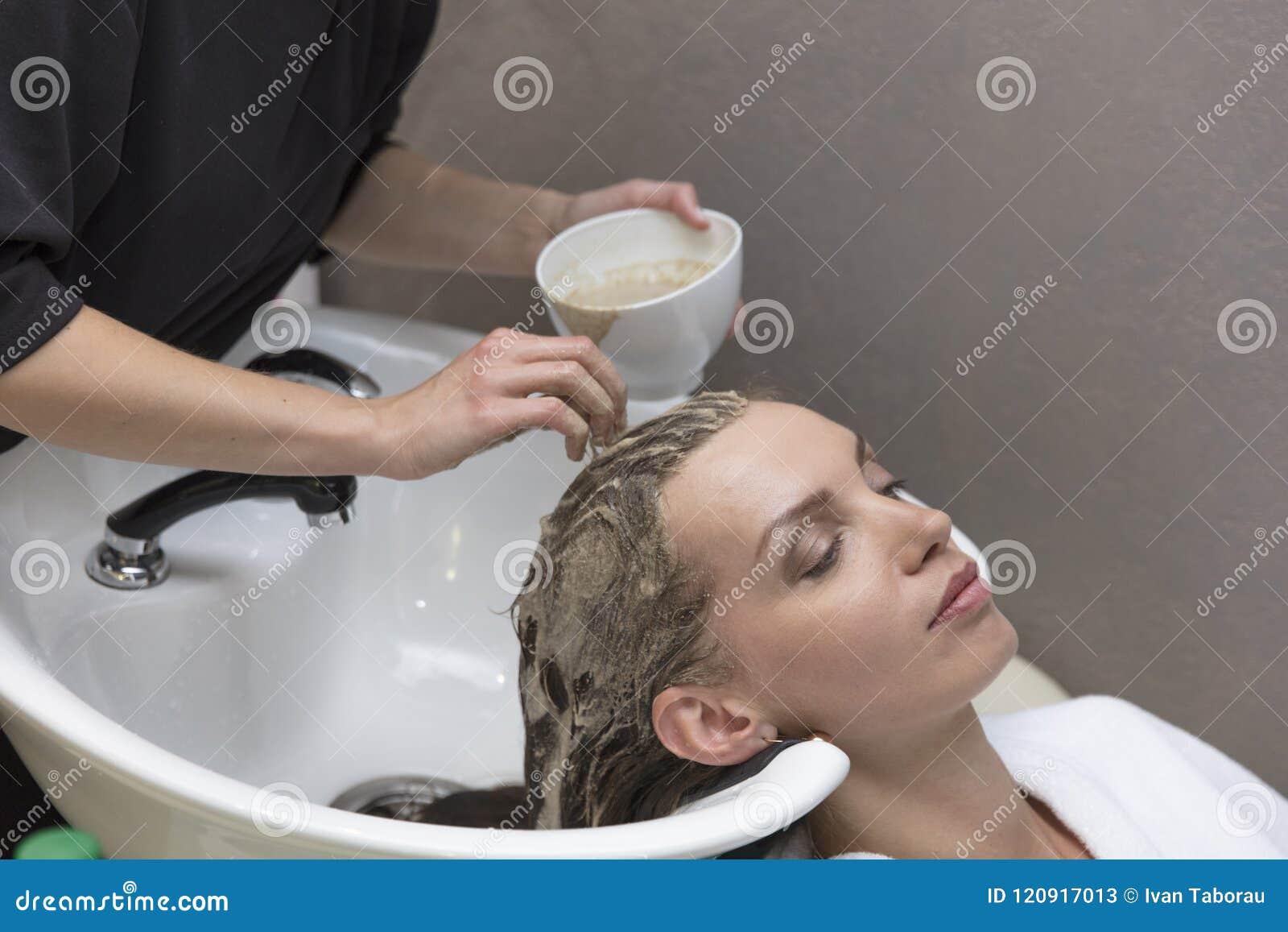 Haarschoonheidsverzorging, vochtinbrengende crèmetoepassing, kapper, haarmasker van een mooie meisje, natuurlijk, een gezondheid