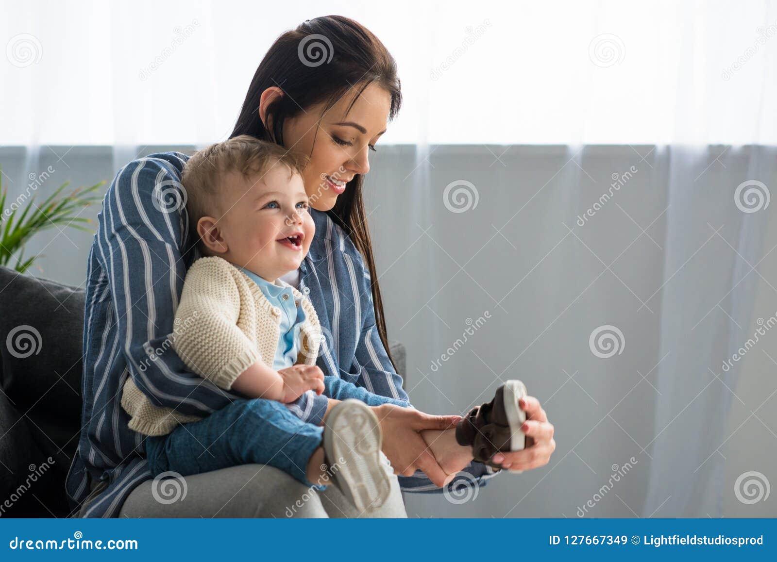 Habillage de mère gai petit bébé sur le sofa