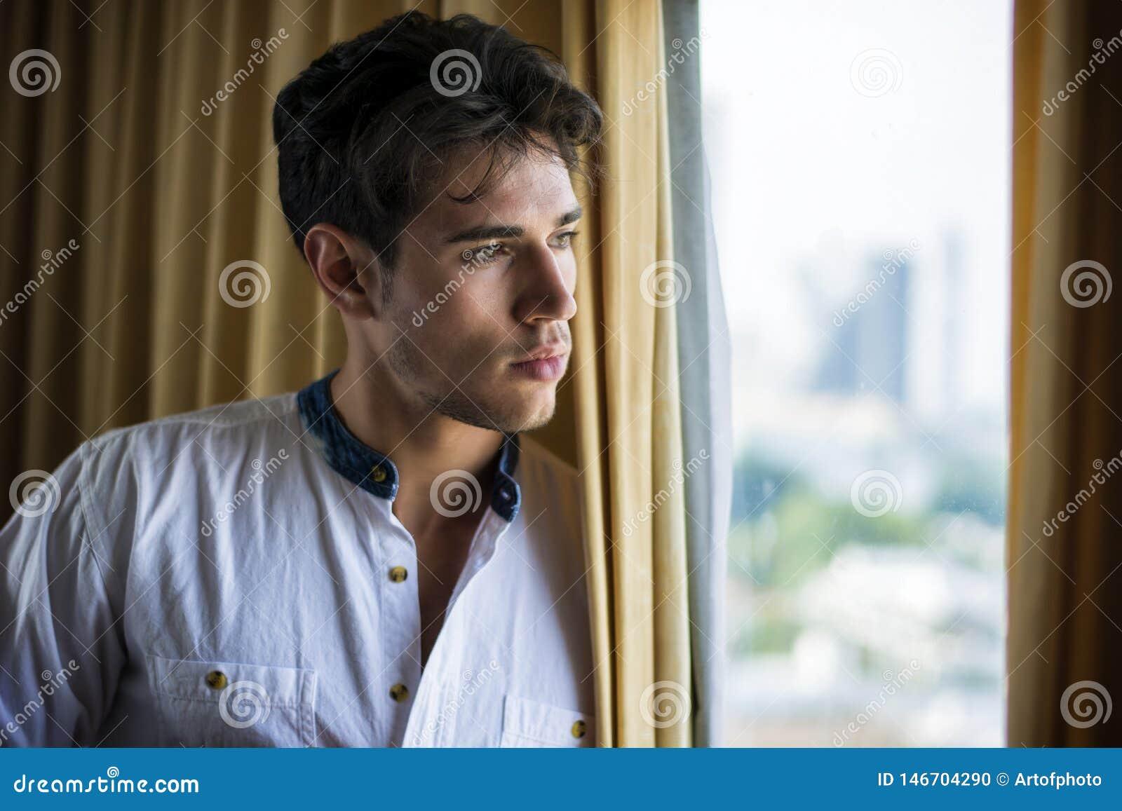 Habillage sexy de jeune homme par des rideaux en fenêtre