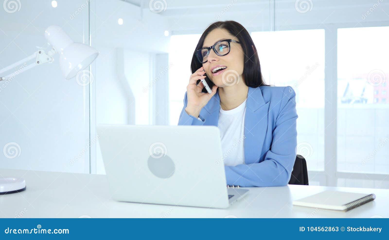 Hablando en el teléfono, empresaria joven que asiste a llamada en el trabajo