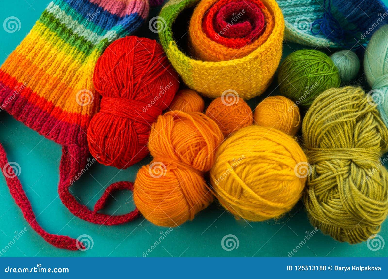 Hacer punto un fondo del azul de la bufanda y del sombrero del arco iris