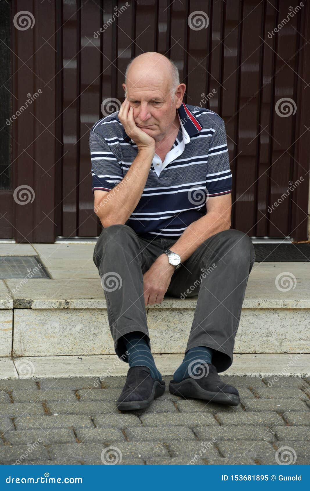 Hacia fuera hombre mayor bloqueado que se sienta delante de su casa