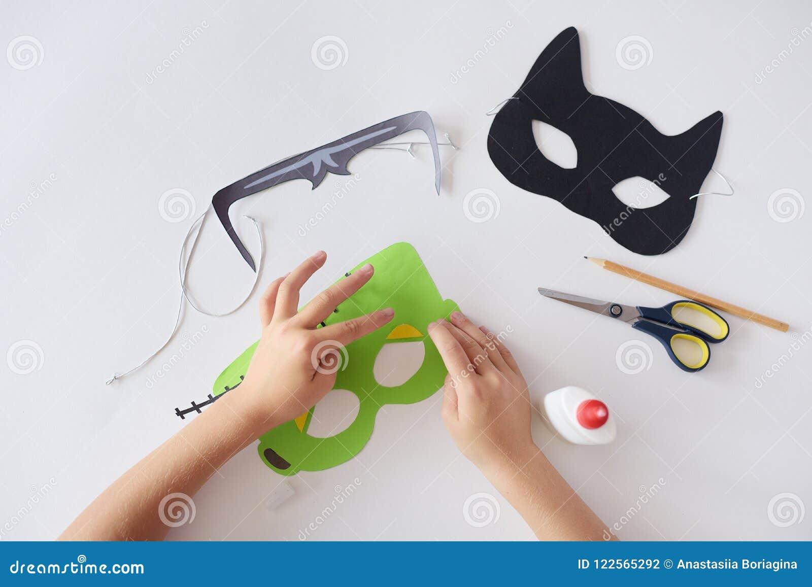 Haciendo las máscaras el ` de papel s del monstruo de Halloween del día de fiesta enmascare las manos del gato negro visión super