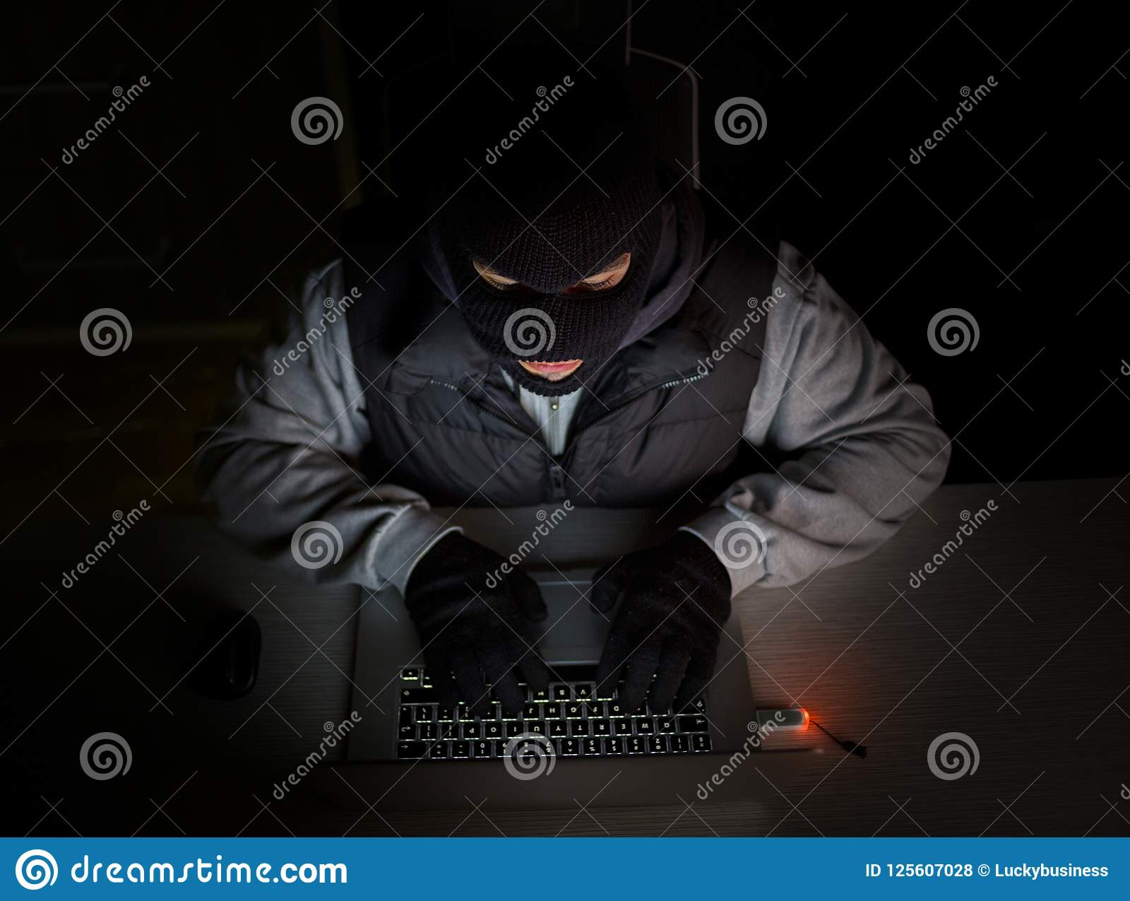Hacker with balaclava typing on laptop
