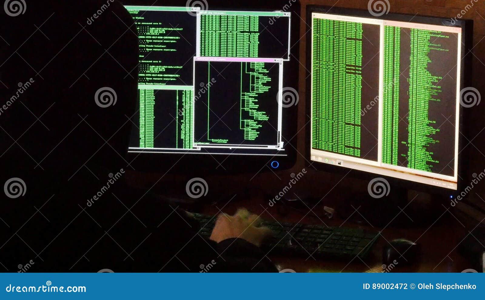 Hacker breaking code. Criminal hacker with black hood penetrating network system from his dark hacker room.