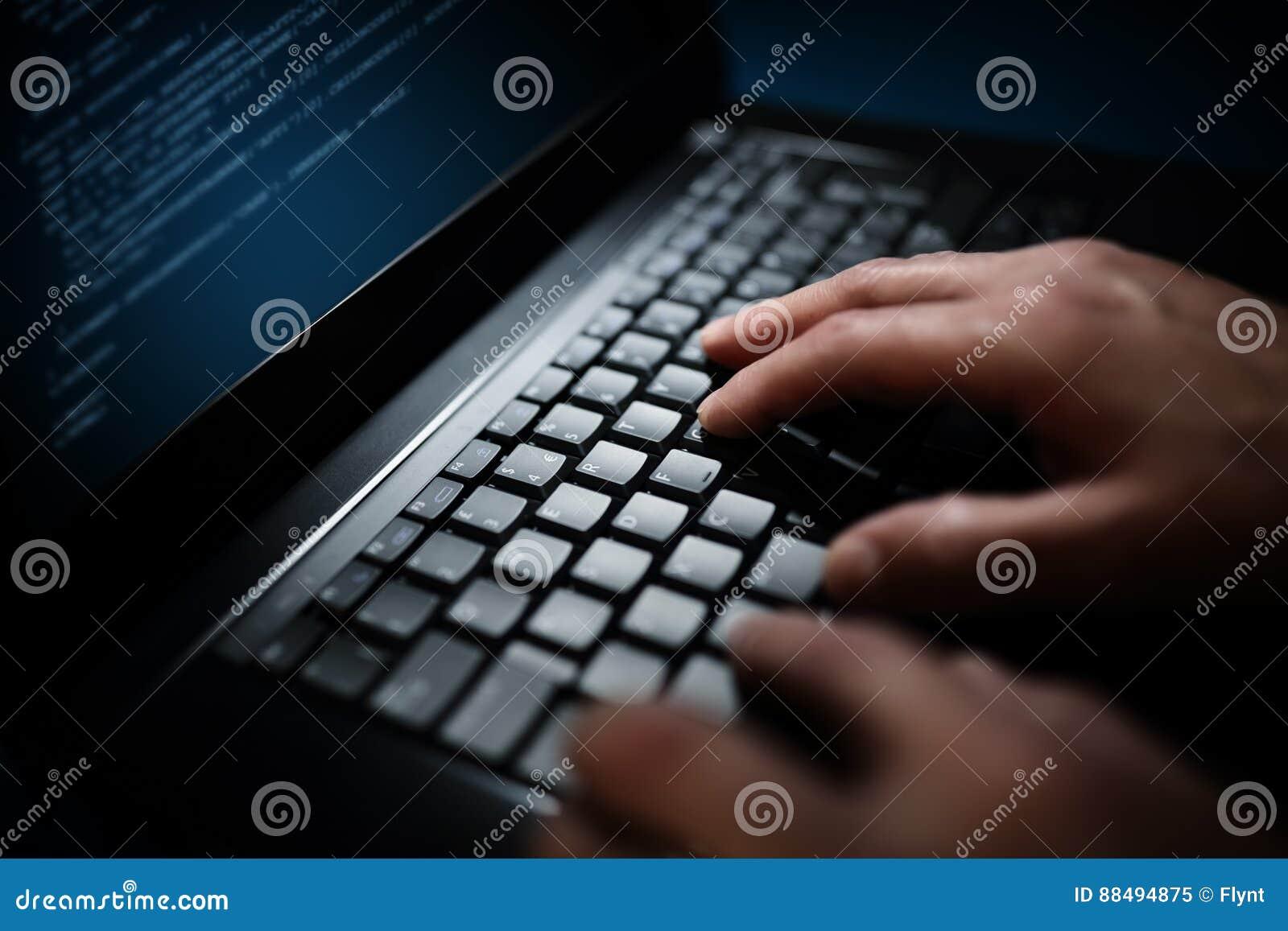Hacker do programador ou de computador que datilografa no teclado do portátil
